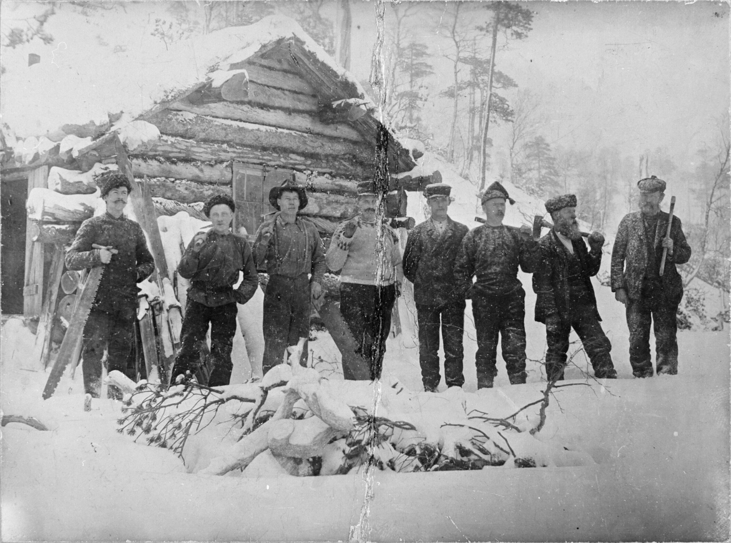 Åtte menn med sag og økser fremfor skogsstue i snø.