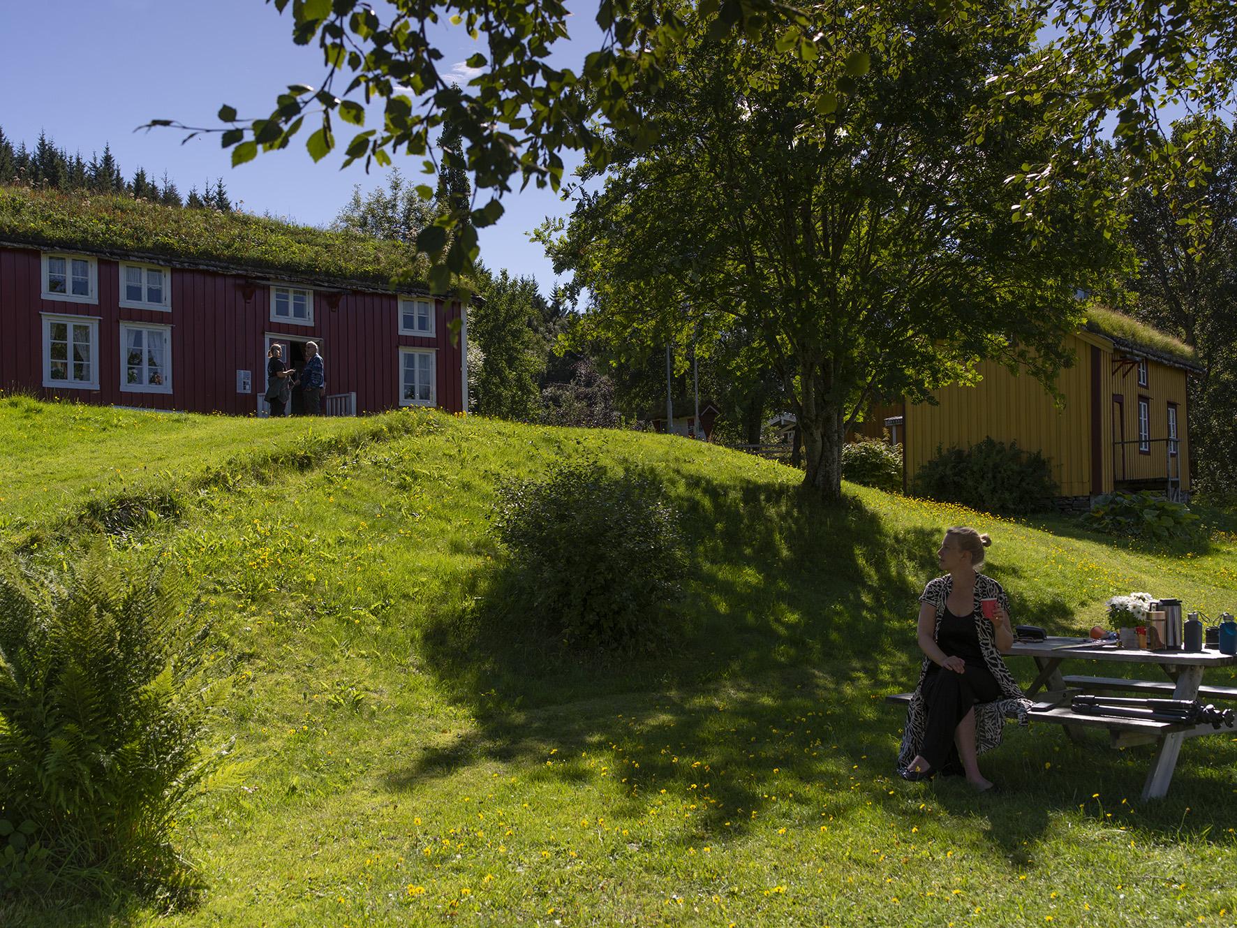 Kvinne på benk på Vevelstad bygdetun