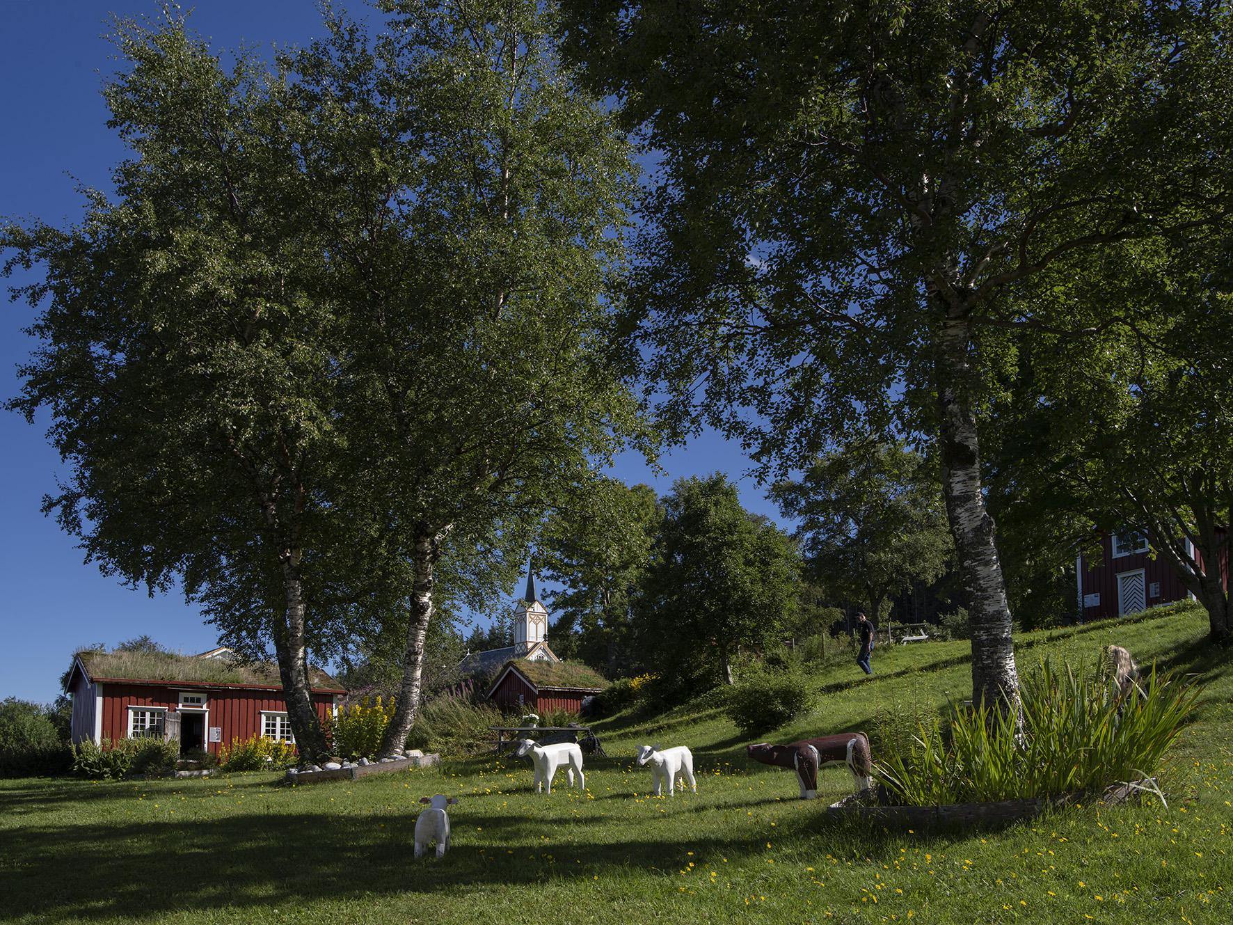 Vevelstad bygdetun, dyrefigurer og kirke i bakgrunn