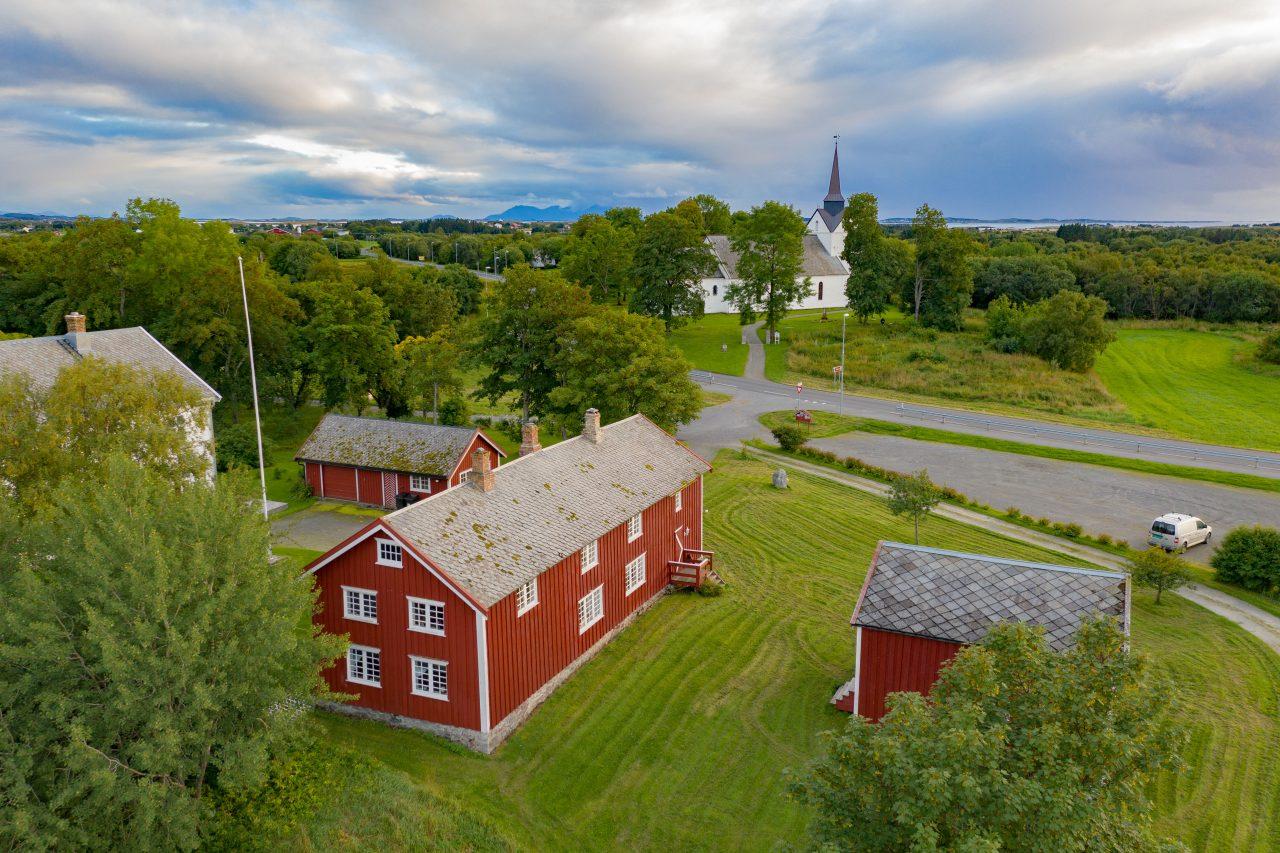Husene på Herøy bygdesamling. Herøy kirke i bakgrunnen