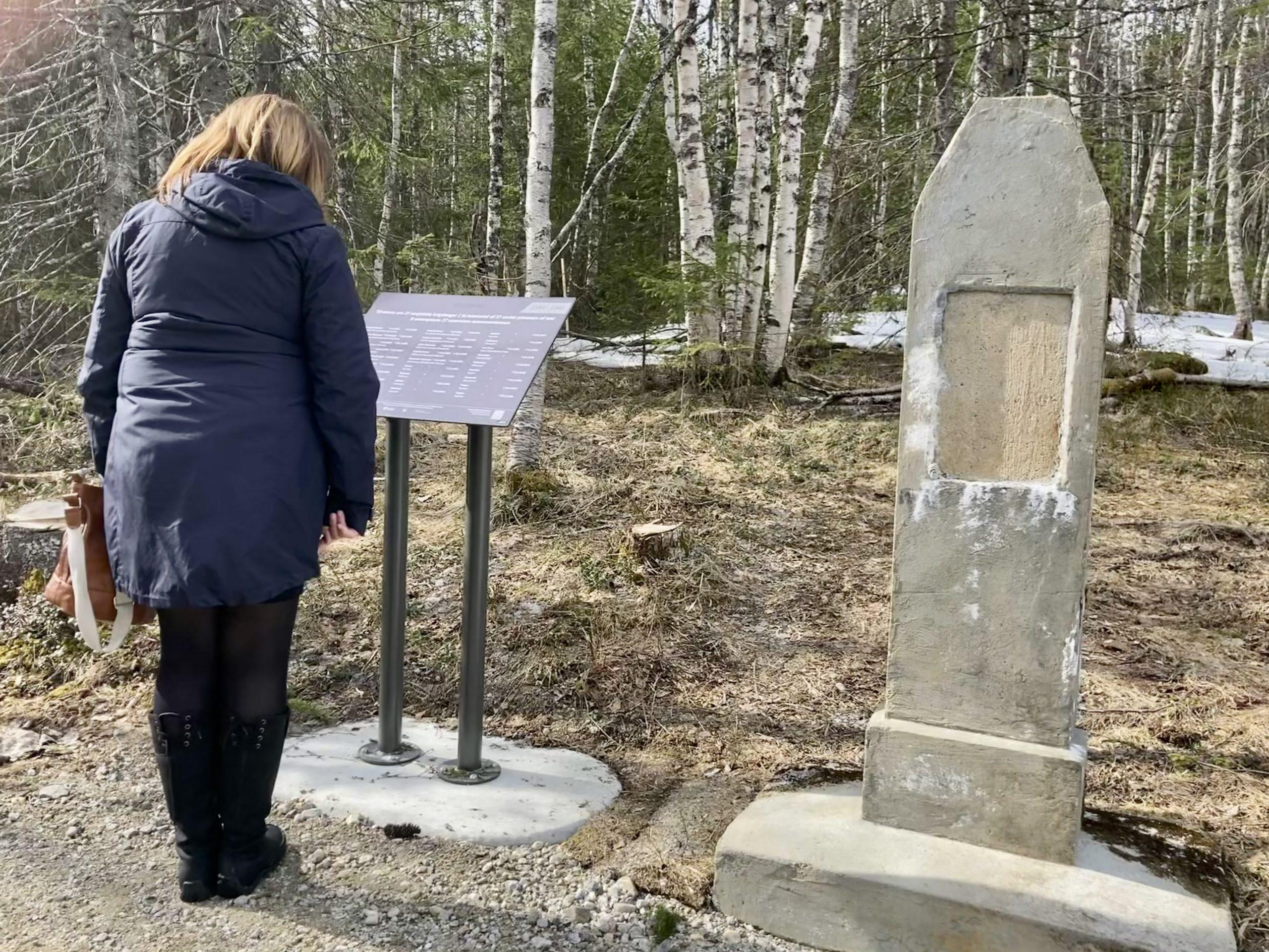 Dame ser på minnestøtten i Dunderland fangeleir